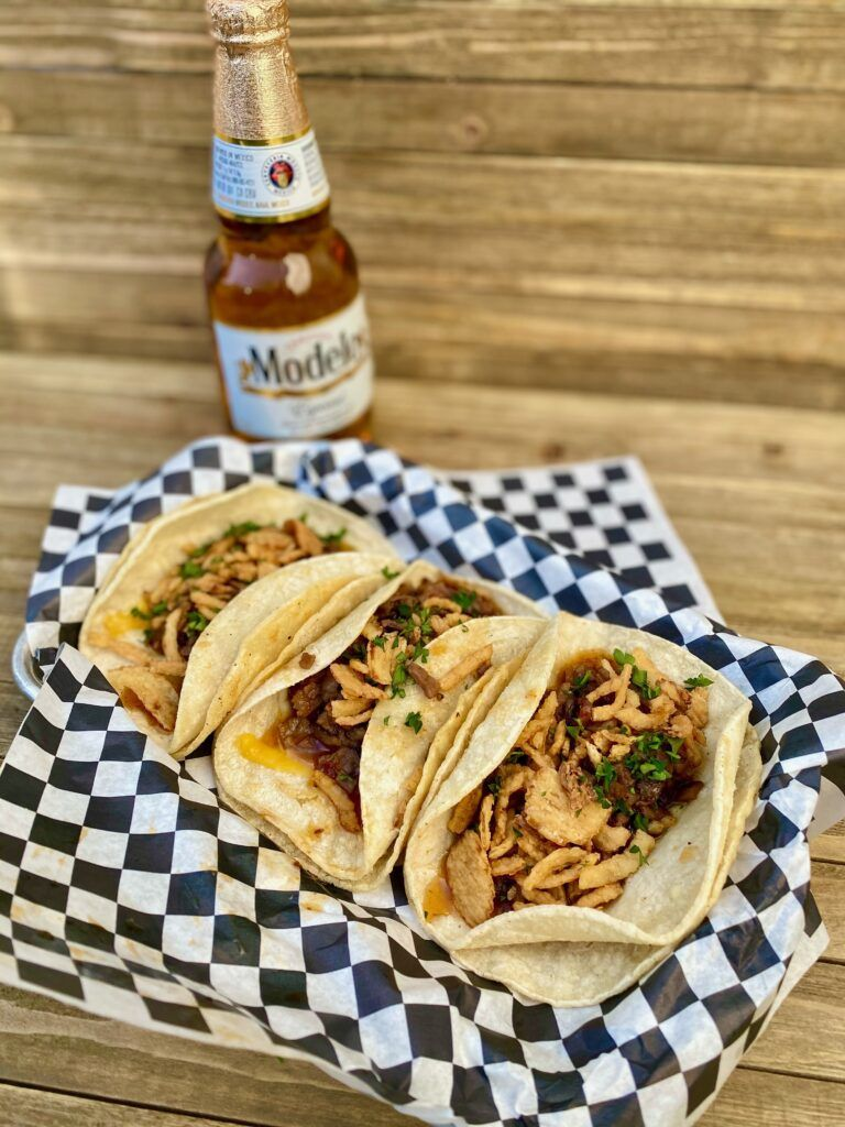 3 tacos with negro modelo in the background